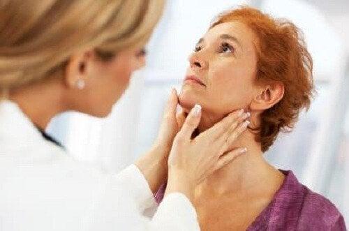 Médico examinando a tireoide