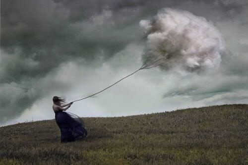 Representação da depressão maior através de mulher puxando uma nuvem pesada