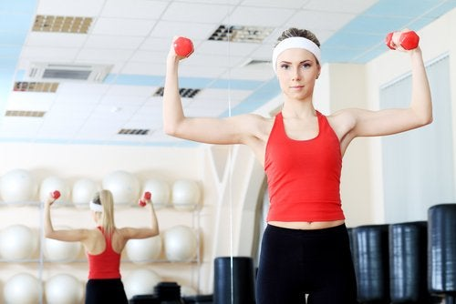 Mulher fazendo exercícios com halteres para firmar os seios