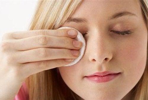 Mulher limpando seu rosto com óleo