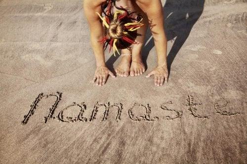 """Palavra """"Namastê"""" escrita na areia"""