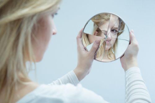 Mulher maltratada se olhando no espelho