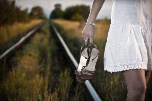 Mulher andando nas vias do trêm arriscando sua vida