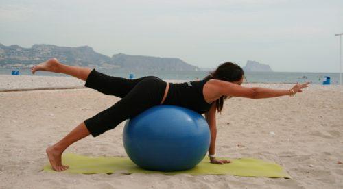 Mulher fazendo exercícios para os glúteos com uma bola