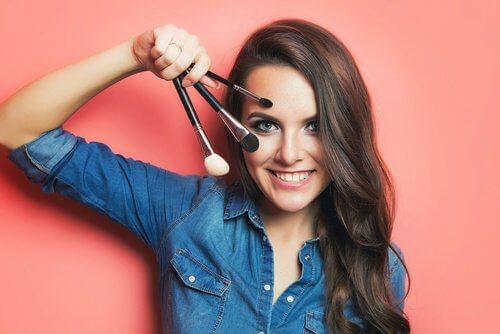 Mulher segurando pincel para maquiagem