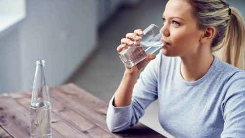 Mulher bebendo água para evitar a má circulação nas pernas