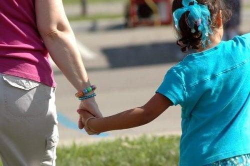 Mãe de mãos dadas com filha