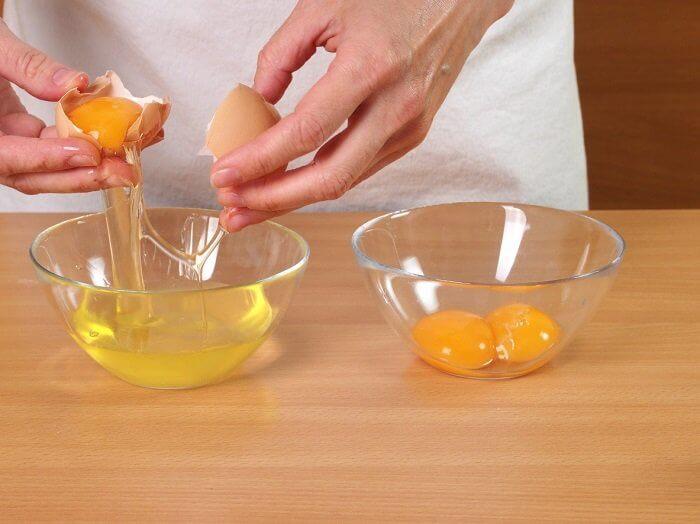 Mulher quebrando ovos em vasilhas