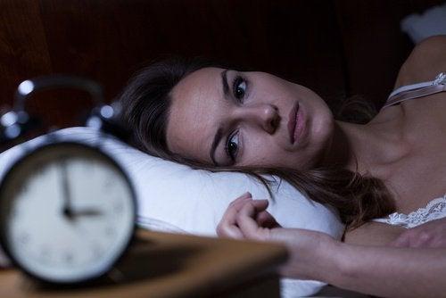 Mulher com insônia, olhando para o despertador