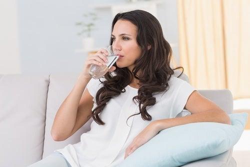 Mulher bebendo agua antes da refeição