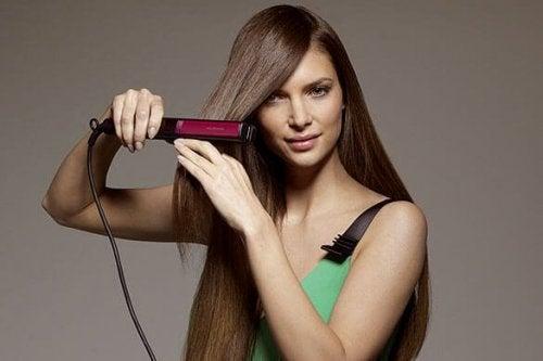 Mulher com chapinha alisando cabelos