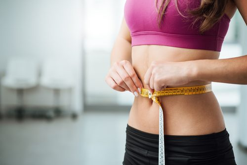 Mulher perdendo peso graças à dieta