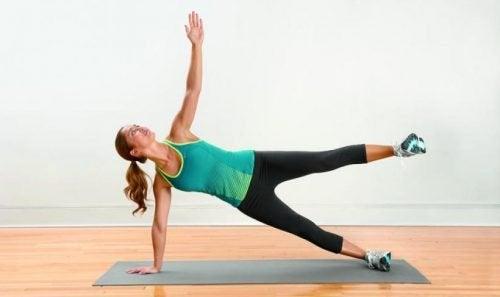 Mulher praticando exercício concha de mariposa para reduzir a dor nas pernas