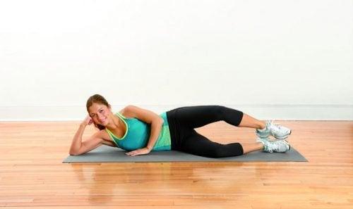 Mulher praticando exercício de elevação de membro inferior para reduzir a dor nas pernas