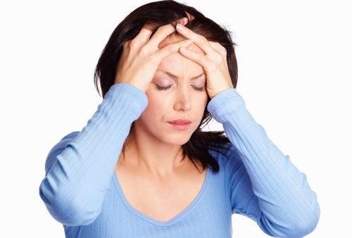 Mulher com dor de cabeça por causa de uma doença cerebrovascular