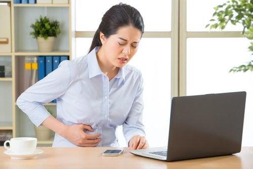 Mulher ao computador com dor de barriga