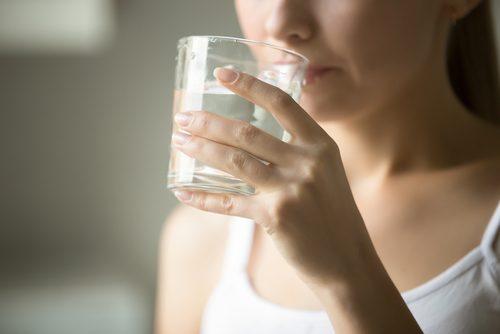 Mulher bebendo bastante água para evitar varizes