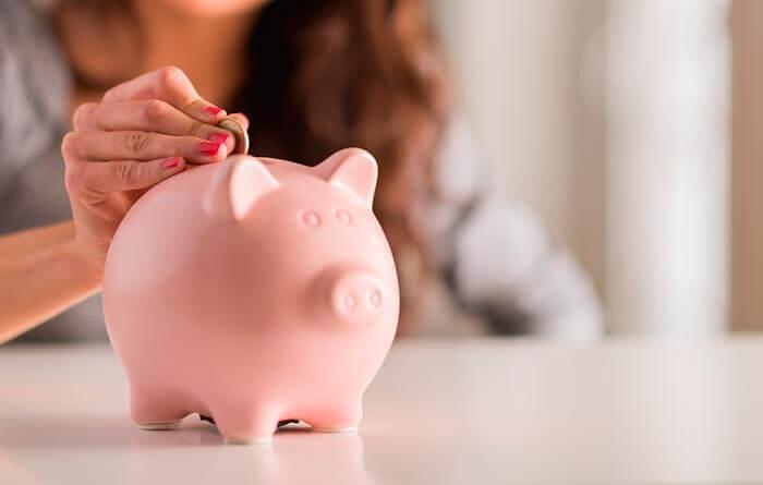 Mulher colocando moeda em porquinho para poupar dinheiro