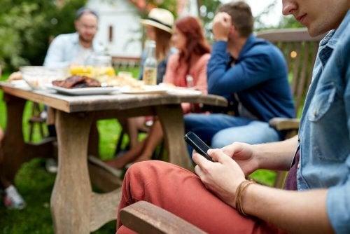 Pessoa usando celular em vez de conversar com amigos