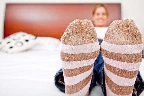 Mulher deitada na cama com meias especiais para evitar má circulação nas pernas