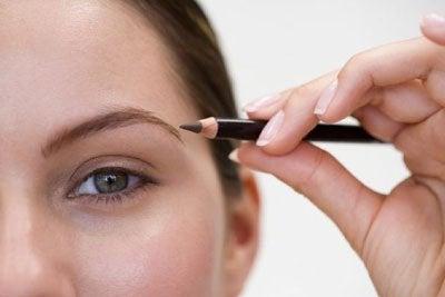 Mulher passando lápis de olho na sobrancelha