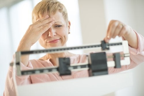 Mulher notando ganho de peso na balança