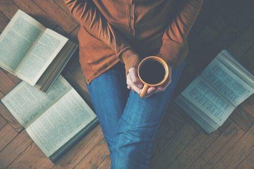 Mulher com uma xícara de café no meio de livros