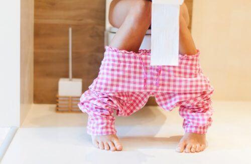 Mulher no banheiro com rolo de papel higiênico