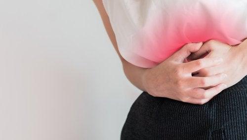 Mulher segurando o ventre sentido dores ou distúrbios menstruais