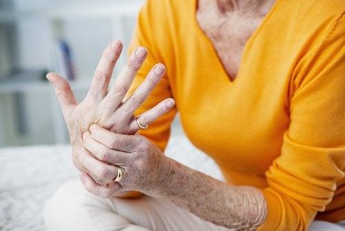 Senhora mexendo na mão, com dor articular