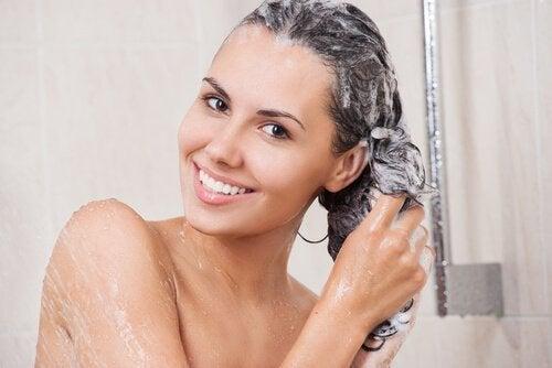 Mulher lavando o cabelo com um shampoo especial para retirar a tinta do cabelo