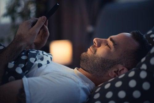 Homem usando celular antes de ir dormir