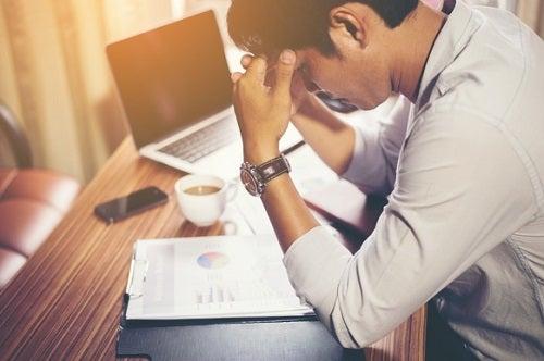 Homem sentindo dor de cabeça no trabalho