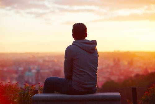 Homem observando por do sol em cidade