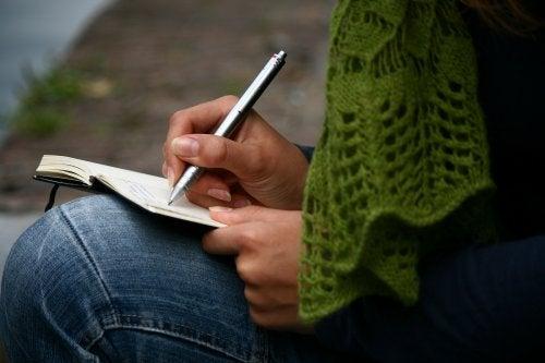 Moça escrevendo as coisas que a tornam orgulhosa