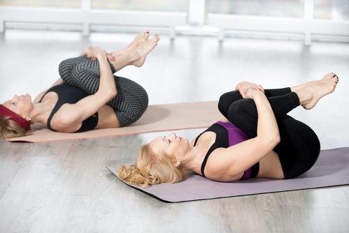 Mulheres fazendo alongamento com joelhos no peito