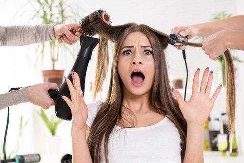 Mulher usando chapinha e secador nos cabelos