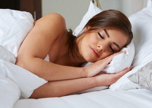Mulher relaxada dormindo em sua cama
