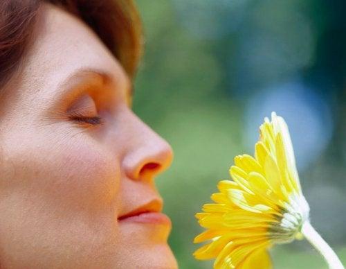Mulher sentindo aroma de flor
