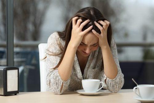 Mulher chorando na mesa da cuzinha