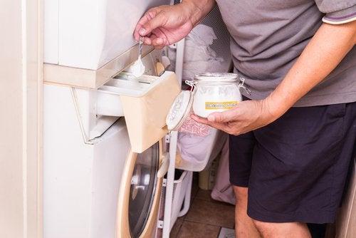 Homem colocando bicarbonato de sódio em máquina de lavar para manter as roupas em perfeito estado