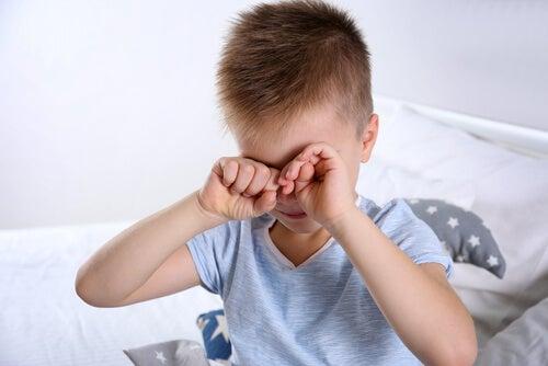 Menino com Síndrome de Asperger acordando, esfregando os olhos