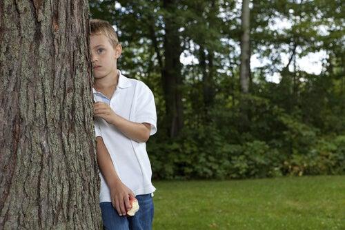 Menino com Síndrome de Asperger se escondendo atrás de árvore