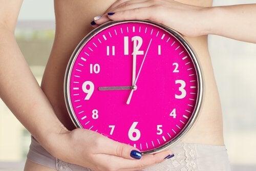 Mulher segurando relógio e controlando a amenorreia ou falta de menstruação
