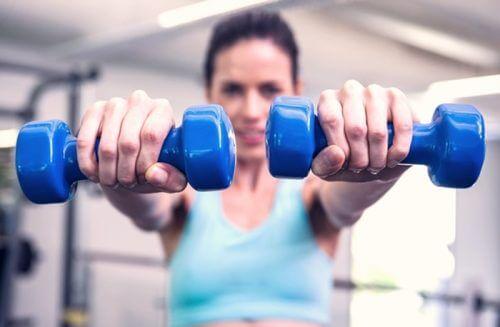Mulher fazendo exercícios com halteres