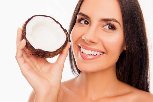 Mulher que usa óleo de coco para branquear seus dentes