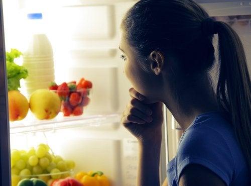 Mulher olhando dentro da geladeira