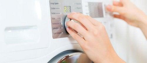 Mulher escolhendo o tipo de lavagem na máquina de lavar