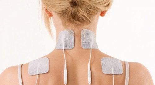 Mulher com eletrodos nas costas e no pescoço para tratar a capsulite