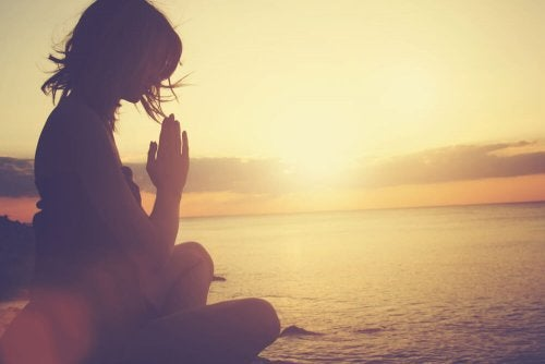 Mulher meditando na praia